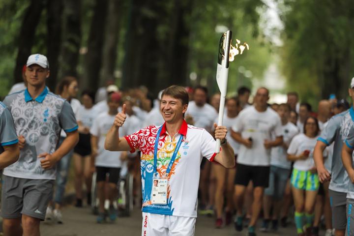 Олимпийский чемпион Алексей Ягудин с факелом эстафеты «Пламя мира» на символического забега #velcombegom в Парке Победы
